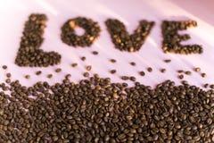 Spilled a rôti des grains de café avec une inscription d'amour Photographie stock
