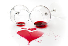 Spilled red wine. Red wine spilled from two turned wineglasses making a heart shape over a white table