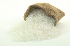 Spilled Rock Salt. Picture of Spilled Rock Crushed Salt from Burlap sack over white background Royalty Free Stock Photo
