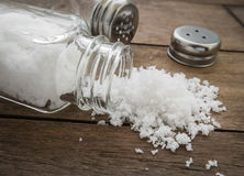 Spilled salt with salt shaker on wooden background Stock Image