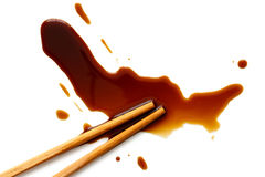 Spilled soya sauce on white with wooden chopsticks from above. Stock Photos