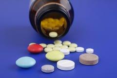 Spilled tablets and medicine bottle. Stock Photo