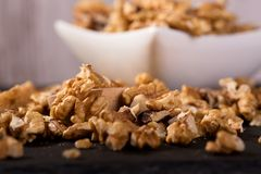 Spilled walnuts in front of square white bowl Stock Images
