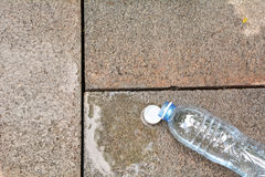 Spilled water with bottle on brick stock illustration