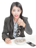Spilling the beans. Young Asian businesswoman at her desk spilling the beans: English idiom and metaphor of betraying a secret or bring out confidential Royalty Free Stock Image
