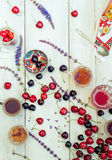 Spilling bright red cherries and drinks Stock Photography