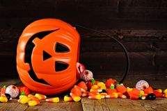 Spilling Halloween Jack o Lantern candy pail on wood Royalty Free Stock Image
