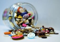 Spilling junk jar. Full of buttons and coins royalty free stock photos