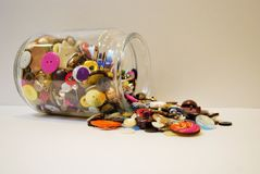 Spilling junk jar. Full of buttons and coins Royalty Free Stock Images