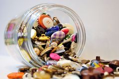 Spilling junk jar. Full of buttons and coins stock photography