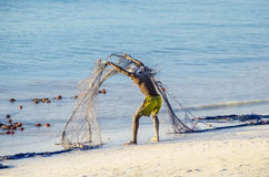 Spilling the net. Fisherman spilling his net, discharging from waste and sand in the evening after work. November 2013. Zanzibar, Tanzania royalty free stock image