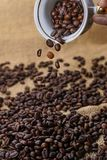Spilling out coffee beans from cup. On sackclothe Royalty Free Stock Image