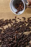 Spilling out coffee beans from cup. On sackclothe Stock Photos