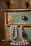 Spilling Pearls. A strand of pearls spills out of a drawer from a gilded, antique jewelry box Royalty Free Stock Photos