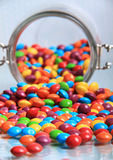 Spilling rainbow sweets. Multi coloured rainbow sweets spilling out of the big sweet jar on to a shiny surface Stock Photo
