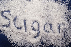 Spilling sugar. Sugar spilling on the blue background Stock Photo