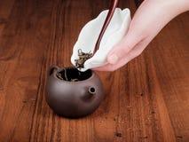 Spilling tea in teapot Stock Photos