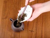 Spilling tea in teapot Stock Photo