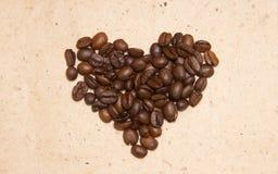 spillt bönakaffe Kaffe i form av hjärtor arkivbild