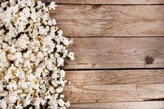 Spillt popcorn på det trä- och retro skrivbordet royaltyfria bilder