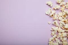 Spillt popcorn på en rosa bakgrund, tomt utrymme för text arkivbild
