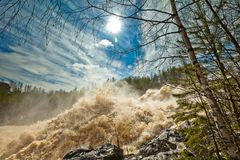 At the waterfall Girvas, Karelia. Sunny day. Spillway from hydroelectric power station in spring. Girvas eruptive crater in Karelia, Russia. Flecks of sunlight Royalty Free Stock Photography
