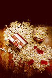 Spilt Tubs of Popcorn and Movie Tickets. High Angle Still Life View of Popcorn Spilling from Toppled Tubs on Rustic Wooden Table with Red Movie Tickets - Cinema Stock Image