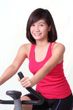 Spin bike lady. Asian lady exercising with a spin bike Stock Photography