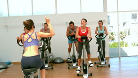 Spin class working out with instructor Royalty Free Stock Image