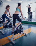 Spin class working out with motivational instructor Stock Image