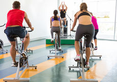 Spin class working out with motivational instructor Royalty Free Stock Photography