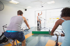 Spin class working out with motivational instructor Stock Photography