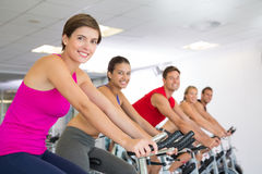 Spin class working out and smiling at camera Stock Image