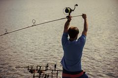 Spin fishing, angling, catching fish. Hobby, vacation, pastime. Fisherman cast fishing rod in lake or river water. Man fish with spinning tackle on summer day royalty free stock photo
