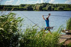 Spin fishing, angling, catching fish. Fisherman cast fishing rod in lake or river water. Man fish with spinning tackle on wooden pier. Adventure, sport royalty free stock image