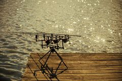 Spin fishing, angling, catching fish. Spinning tackles on pod on wooden pier. Fishing, adventure, sport, activity. Rods and reels at river or lake water Stock Image