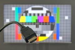 Spina del cavo di HDMI davanti all'immagine della prova di visualizzazione della TV immagini stock libere da diritti