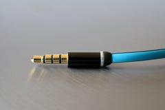 Spina di presa nera e dorata con cavo blu Fotografia Stock