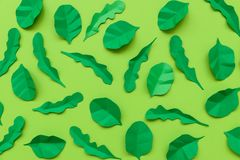 Spinach and arugula leaves made from paper on green background. Minimal, creative, vegan, healthy or food art concept. Flat lay. Top view royalty free stock photos