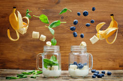 Spinach banana and blueberry banana smoothie with flying slices. On a wood background. toning. selective Focus Royalty Free Stock Photo
