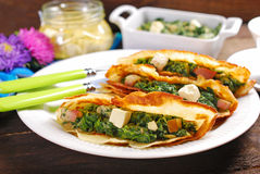 Spinach and feta filled pancakes on wooden table Stock Photo