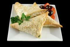 Spinach And Feta Triangles. Spinach and feta cheese triangles with olives and cherry tomatoes Royalty Free Stock Image