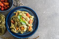 Spinach fettuccine with tomatoes. Italian food style royalty free stock images