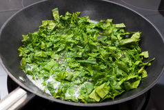 Spinach on frying pan Stock Photography