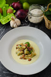 Spinach gnocchi with parmesan sauce topped with bacon Stock Photos
