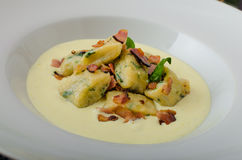 Spinach gnocchi with parmesan sauce topped with bacon Royalty Free Stock Photography