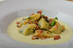 Spinach gnocchi with parmesan sauce topped with bacon Royalty Free Stock Image