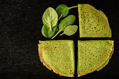 Spinach green pancakes crepes on black background. Stock Image
