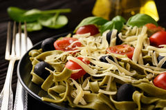 Spinach green pasta with olives, tomatoes and cheese. Royalty Free Stock Photo