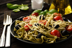 Spinach green pasta with olives, tomatoes and cheese. Royalty Free Stock Photography